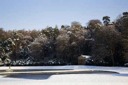 The Temple of Piety under snow, seen over the Half-Moon pond at Studley Royal Water Garden, North Yorkshire