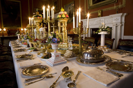 Close view of the Dining Room table with silverware and floral decoration, and period food details at Attingham Park, Shrewsbury, Shropshire