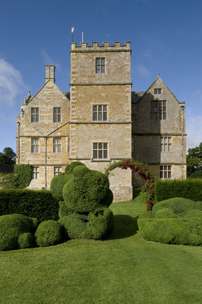 The east front of Chastleton House, Oxfordshire, on a summer morning with the unusual topiary in the foreground