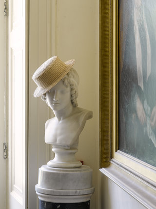 Sculpture bust with a staw hat at a jaunty angle, in the Entrance Hall at Greenway, Devon, which was the holiday home of the crime writer Agatha Christie between 1938 and 1976