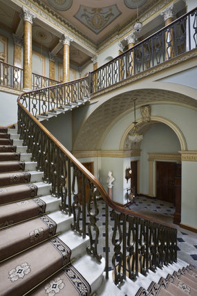 The sweeping staircase with bronzed balustrading in the Staircase Hall at Berrington Hall, Herefordshire
