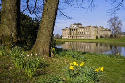 The south front of Lyme Park seen across the lake, in springtime
