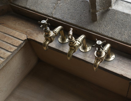Brass taps on the teak sink, against the granite window, in the Butler's Pantry at Castle Drogo, Devon