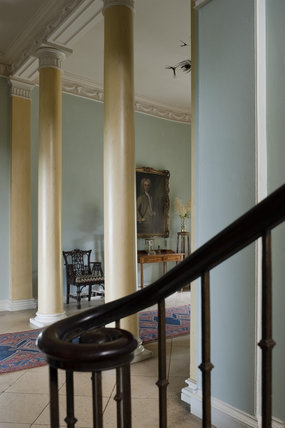 Detail of the wrought iron balustrade of the staircase, and the two Doric columns beyond, of the Entrance Hall at Newark Park, Gloucestershire