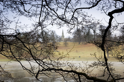 A winter view through bare tree branches towards the spire of the Victorian St Mary's church designed by William Burges built in 1871 -78 on the estate at Studley Royal Water Garden