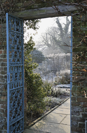 Looking through an ornamental wrought iron gate to the Rose Garden in January at Sissinghurst Castle Garden, near Cranbrook, Kent