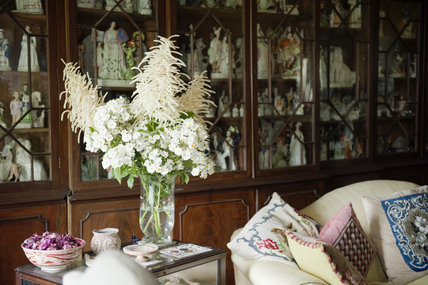 Flower arrangement in front of an eighteenth century mahogany bookcase filled with Staffordshire ceramic figures, in the Drawing Room at Newark Park, Gloucestershire