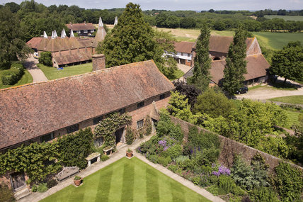 The view from the Elizabethan Tower at Sissinghurst Castle looking north, north west over the front range, restaurant and oast-houses in June
