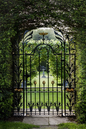 View through a decorative wrought-iron gate into the summer garden at Antony, Cornwall
