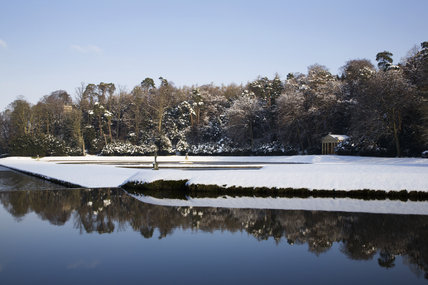 The Temple of Piety under snow, seen over the Canal and Half-Moon pond at Studley Royal Water Garden, North Yorkshire