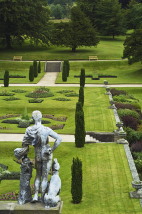 The lead figure of Meleager over looking the Orangery Terrace with clipped irish yew trees at Lyme Park, Cheshire