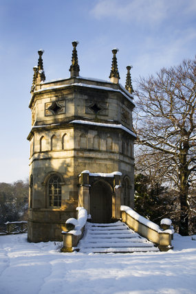 The Octagon Tower under snow on the valley side at Studley Royal Water Gardens, North Yorkshire