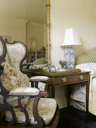 Armchair, Victorian giltwood and gesso overmantel mirror c.1860 and bedside table in Agatha Christie's Bedroom at Greenway, Devon, which was the holiday home of the crime writer Agatha Christie between 1938 and 1976.