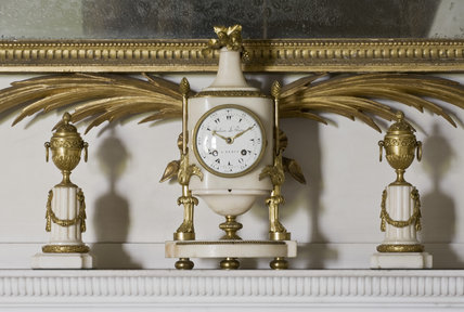 A Louis XV white marble clock by Julien Leroy flanked by a pair of casolettes (reversible urn candlesticks) on the mantelpiece in the Drawing Room at Berrington Hall, Herefordshire