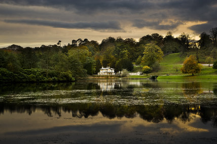 View across the lake at dusk at Studley Royal Water Garden laid out by John Aislabie in 1716-40, next to Fountains Abbey, North Yorkshire