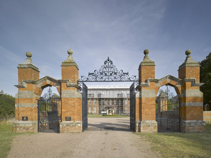 Outdoor conservation - view through the wrought iron entrance gates to the house with scaffolding erected working on the roof at Hanbury Hall, Worcestershire