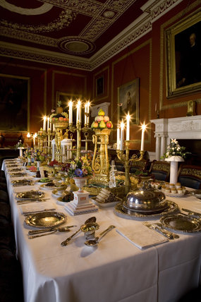 The Dining Room at Attingham Park, Shrewsbury, Shropshire, with the dining table laid for a formal dinner and with table decorations and candelabra
