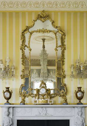 A giltwood pier glass in George II style surmounts the fireplace in the Drawing Room at Hinton Ampner, Hampshire
