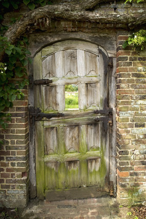 Charming wooden gate with a central window, which leads to Bustalls (the old calf pens) and other parts of the garden at Barrington Court, Somerset
