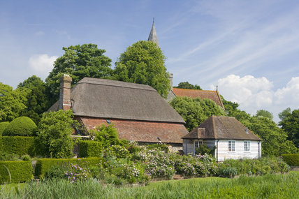 A view towards the back of Alfriston Clergy House, a fourteenth-century Wealden hall house in a cottage style garden in East Sussex