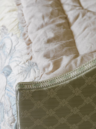 Close view of part of the bed with upholstered head and footboard, and quilt, which is a recreation of Agatha Christie's bed in the Bedroom at Greenway, Devon, which was the holiday home of the crime writer Agatha Christie between 1938 and 1976