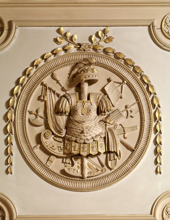 A detail of armorial trophy in roundel above door in the Marble Hall
