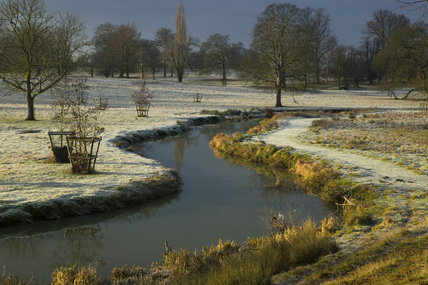 A frosty December view of the River Dene which joins with the River Avon in the deer park at Charlecote Park, Warwickshire