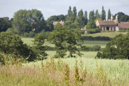View to the castle and barn at Sissinghurst, over farmland which is part of a new project which aims to reconnect the garden at Sissinghurst with the surrounding farm landscape