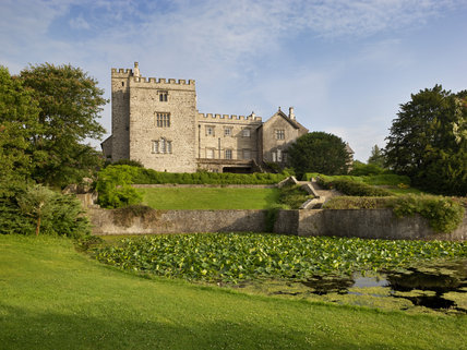 A view across the lake and garden to the south east front of Sizergh Castle, near Kendal, Cumbria