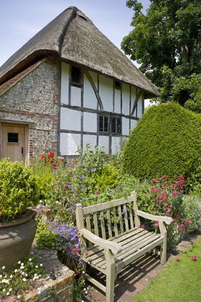 Alfriston Clergy House, a fourteenth-century Wealden hall house, with a wooden bench in a cottage style garden in East Sussex