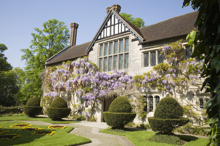The fifteenth-century Courtyard range of Baddesley Clinton, West Midlands with a pretty wisteria climbing the timbered facade