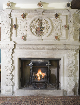 The heraldic stone chimneypiece in the Great Hall at Baddesley Clinton, West Midlands