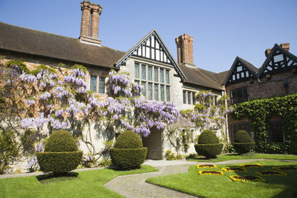 The fifteenth-century Courtyard range of Baddesley Clinton, West Midlands with a pretty wisteria climbing the stone facade