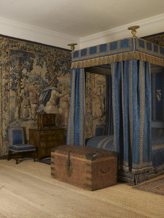 The Blue Room at Hardwick Hall, Derbyshire, with the Morocco leather covered nailed trunk c.1660-1720 at the foot of the bed. This type of trunk is particularly associated with offices of state and has royal crowns on the hasps.