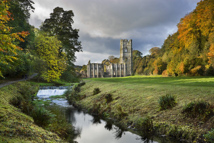 A view along the River Skell in autumn towards Fountains Abbey, North Yorkshire, a Cistercian community of monks from the twelfth century until the Dissolution in 1539