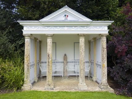 Neo-classical temple with columns and pedimented roof, built as a folly, gazebo and resting-place in the garden at Hinton Ampner, Hampshire