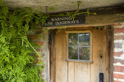 Warning sign on the low doors at Alfriston Clergy House,  in East Sussex