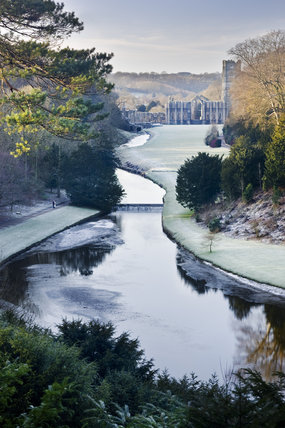 Looking over the Half Moon Pond and weir of Studley Royal Water Garden in winter, from the Surprise View towards Fountains Abbey, North Yorkshire