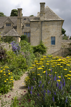 View of the house over the Long Border with a blue and yellow summer planting including Achillea at Snowshill Manor, Gloucestershire