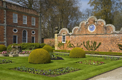The Victorian Parterre garden and beyond it, the cusped gable wall and clock brought from Stansty Park at Erddig, Wrexham, Wales