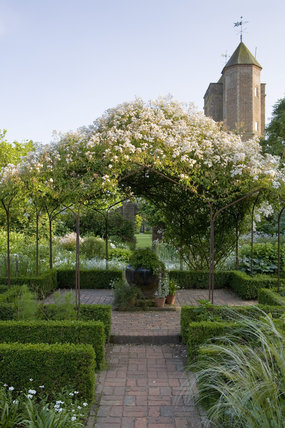 The White Garden in summer with Rosa mulliganii covering the pergola, and the Elizabethan Tower in the distance at Sissinghurst Castle Garden, near Cranbrook, Kent