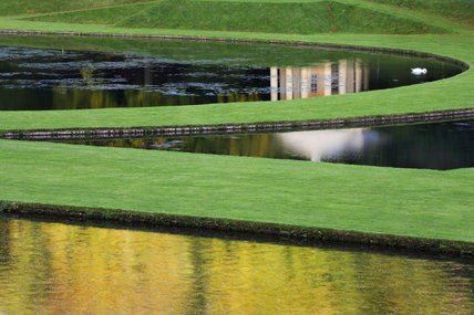 Reflection of the Temple of Piety with pediment and Tuscan columns, seen in the waters of the Canal and Half-Moon pond, at Studley Royal Water Garden, North Yorkshire