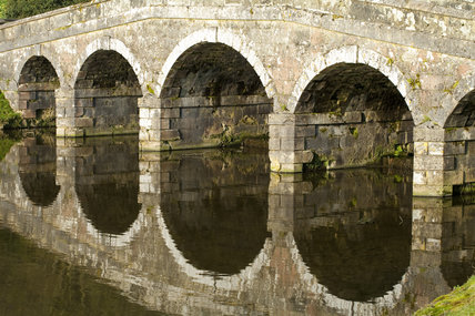 Close view of the arches of the Palladian Bridge reflected in the lake at Stourhead, Wiltshire