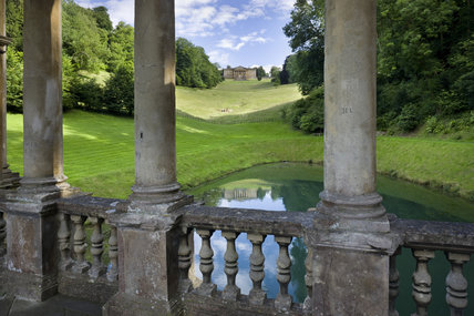 View through the columns of the loggia of the Palladian Bridge towards the House (not owned by the NT) at Prior Park Landscape Garden, Bath