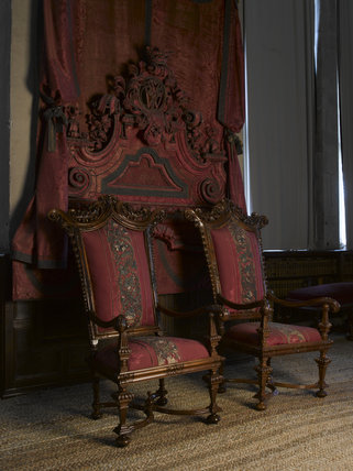The pair of carved walnut high-backed chairs placed under the canopy in the Gallery at Hardwick Hall, Derbyshire