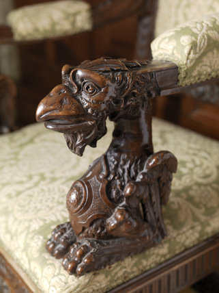 Detail of the carved armrest of a chair in the Teak Staircase hall at Lanhydrock, Cornwall