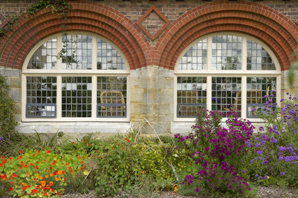 Flowers in front of the conservatory windows at the house designed by Philip Webb in the Arts & Crafts style in 1892-4 at Standen, East Grinstead, West Sussex