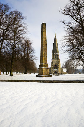 Snow on the estate at Studley Royal Water Garden created by John Aislabie in the eighteenth century adjoining Fountains Abbey, North Yorkshire with the Obelisk, 1815, and St Mary's church