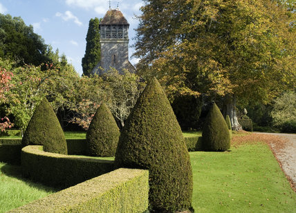 A view to All Saints Church through the topiary shapes and hedging in The Orchard at Hinton Ampner, Hampshire