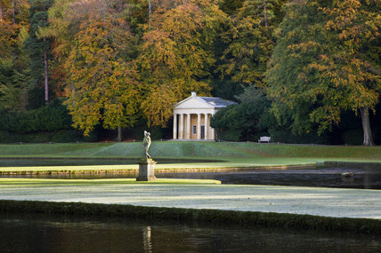 The Temple of Piety with pediment and Tuscan columns, seen over the Canal and Half-Moon pond, and the statue of Bacchus in front, at Studley Royal Water Garden, North Yorkshire